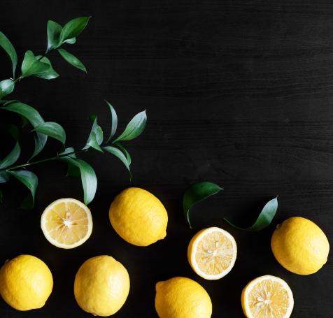 Fresh yellow lemons on black background